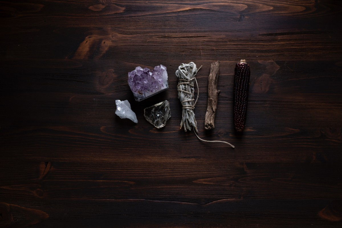 sage, crystal and other objects lying on wooden table