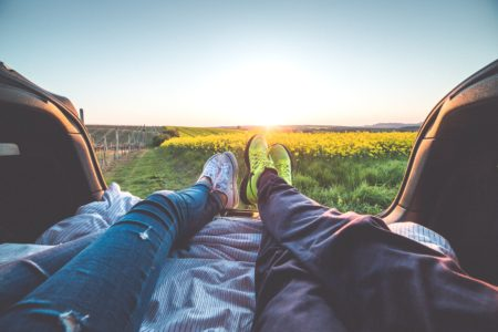 man and woman's feet coming out of back of trunk overlooking garden of flowers with a sunset