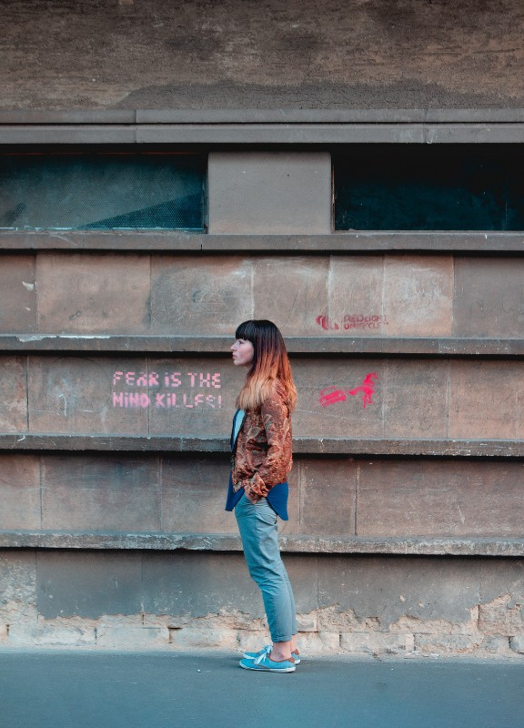 "girl standing by graffiti that says ""fear is the mind killer"""