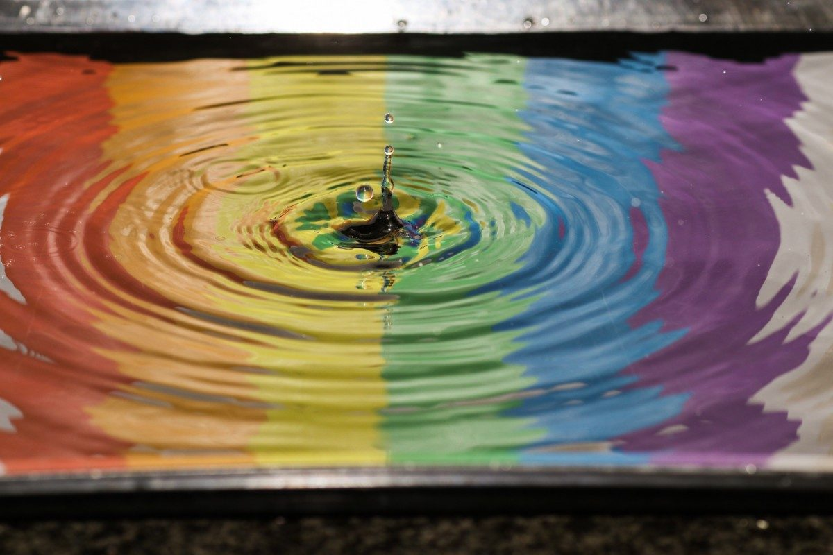 reflection of a rainbow in a puddle of water lgbtq